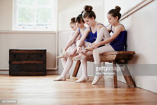 Female ballet dancers putting on shoes in hall