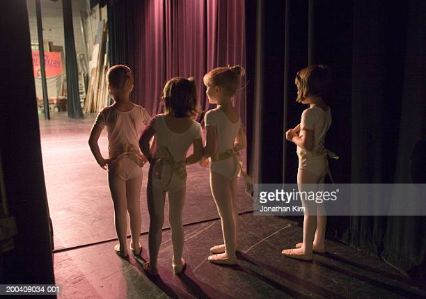 female ballet students (4-6) watching from backstage, rear view - dietro le quinte palcoscenico foto e immagini stock