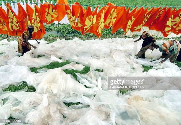 Female Bangladeshi labourers arrange plastic sheeting to dry in the sun on a roadside in the Rasulpur District of Dhaka, 23 September 2005. - The...