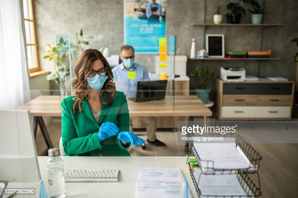 female bank employee sitting at desk and putting on gloves in office - surgical glove stock pictures, royalty-free photos & images