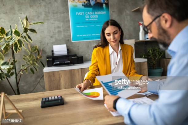 female bank manager working on graphs with her employee in office - economist stock pictures, royalty-free photos & images