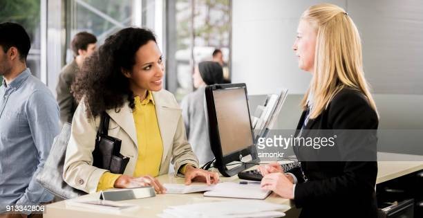 female bank teller advising female customer - cashier stock pictures, royalty-free photos & images