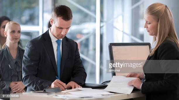 Vrouwelijke bank teller mannelijke klant helpen met documenten die hij nodig heeft om te ondertekenen