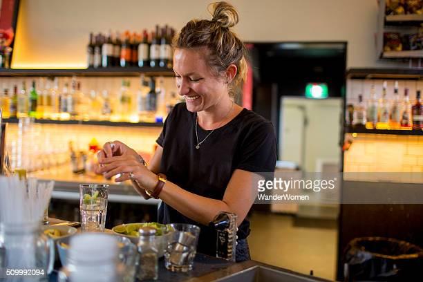 Female bar tender behind bar making a drink