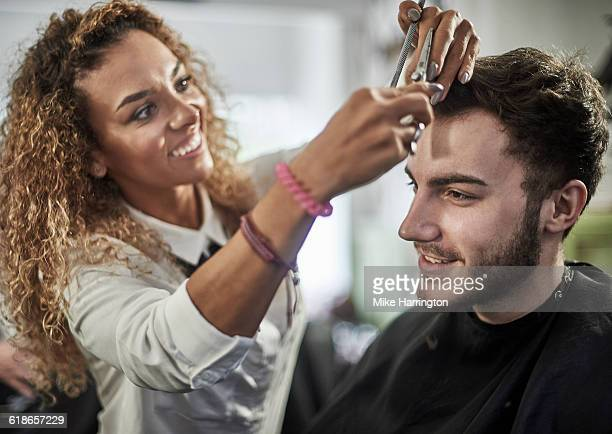 Female barber perfecting hair cut
