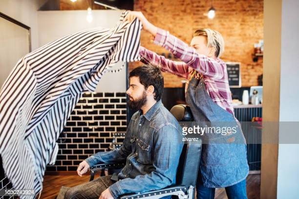 female barber spreading cape on customer in salon - cape garment stock photos and pictures