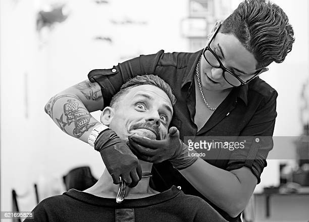 Female barber tattooed woman styling attractive threatening moustachioed male victim