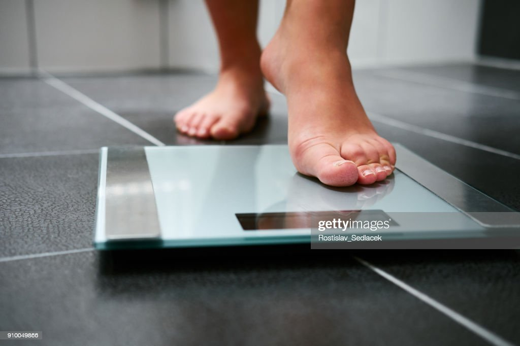 Female bare feet with weight scale : Stock Photo