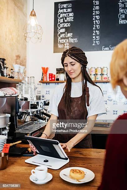 Female barista cashier in a cafe
