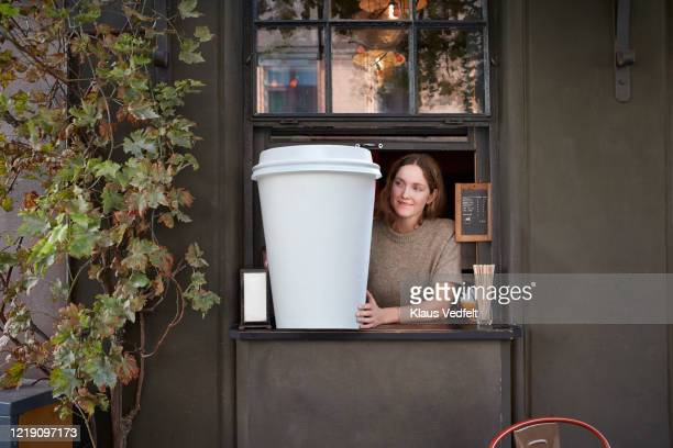 female barista holding disposable coffee cup at take out counter of cafe - funny customer service stock pictures, royalty-free photos & images