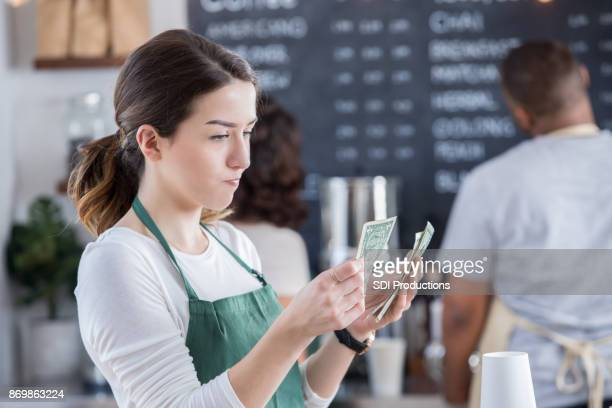 Female barista is disappointed with her tips