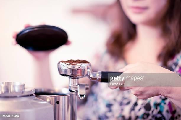 Female barista leveling coffee powder.