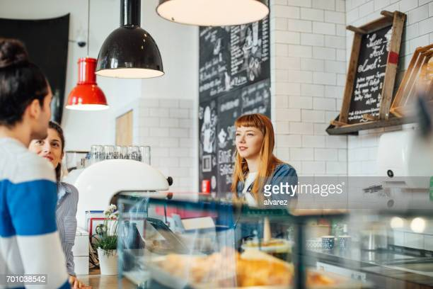 Female barista looking at customers in coffee shop