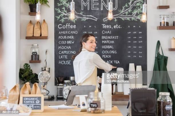 female barista looks over her shoulder - menu stock pictures, royalty-free photos & images