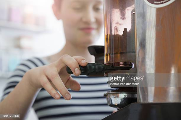 Female barista making coffees with expresso maker machine in cafe.
