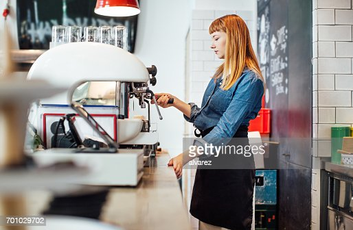 Female barista operating coffee maker in cafe