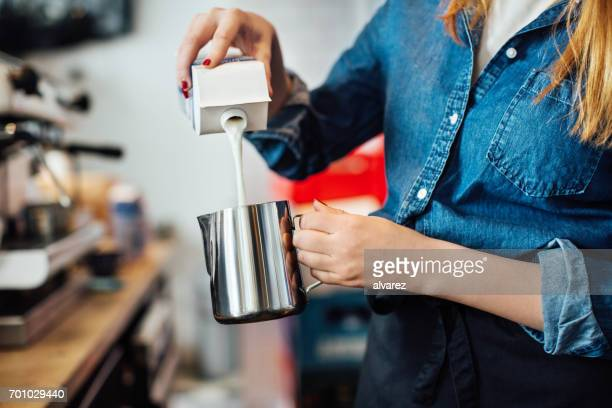 Female barista pouring milk into jug at cafe