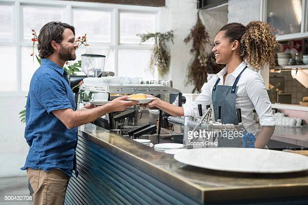 Female barista serving food to mid adult man in cafe