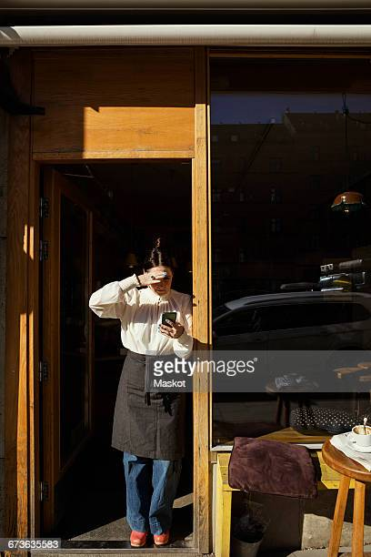 Female barista shielding eyes while using phone at doorway on sunny day
