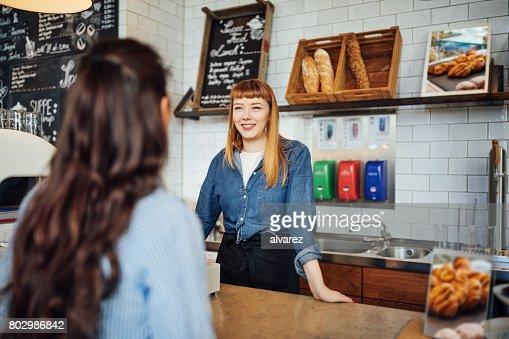Female barista using cash register in cafe
