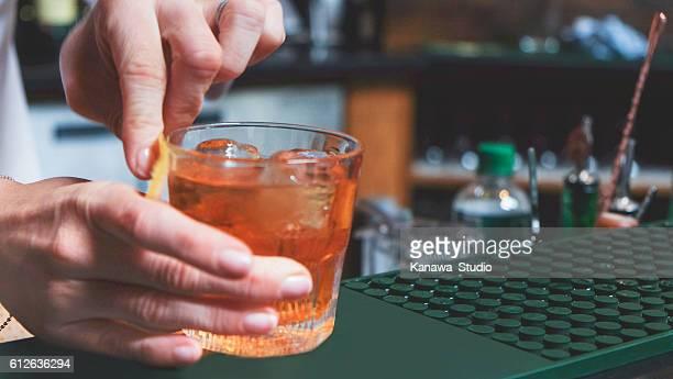 Female bartender making whiskey cocktail