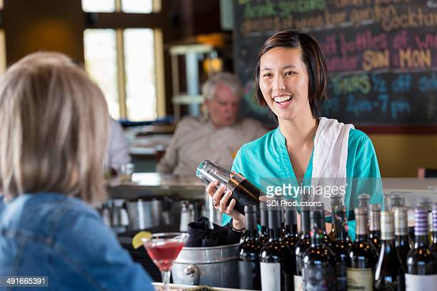 Female bartender mixing drink and conversing with customer