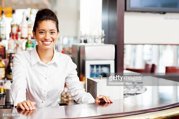 Female Bartender Standing At Counter