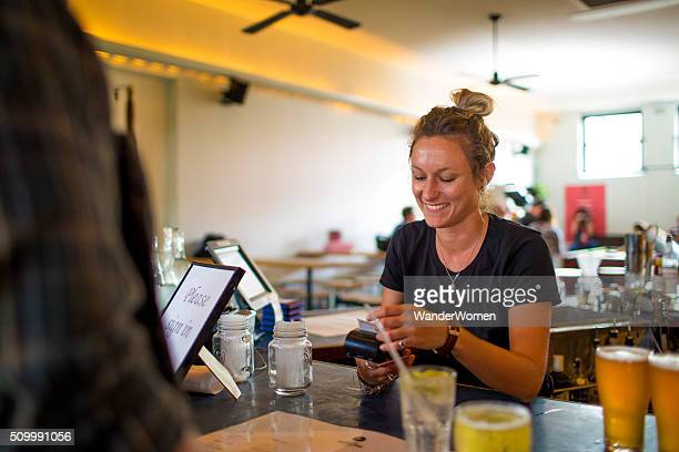 Female bartender taking electronic payment transfer behind bar