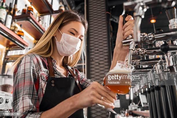 weibliche bartender trägt schützende gesichtsmaske, serviert ein bier während der coronavirus-pandemie - corona beer stock-fotos und bilder