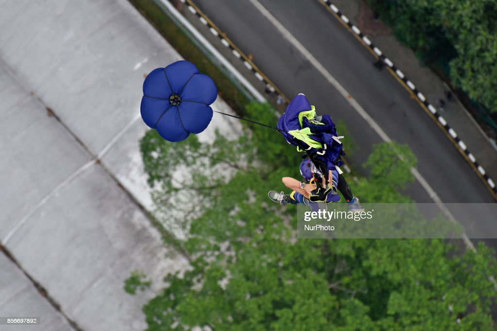A female base jumper leaps off the 300-meter-high Kuala Lumpur tower