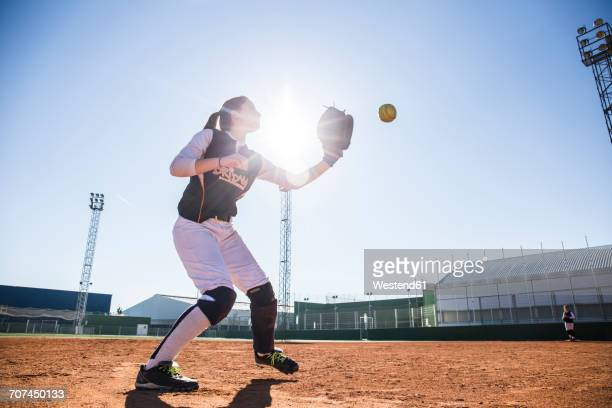 Female baseball player catching the ball during a baseball game