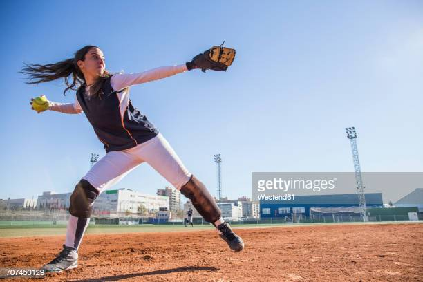 female baseball player throwing the ball during a baseball game - baseball pitcher stock pictures, royalty-free photos & images