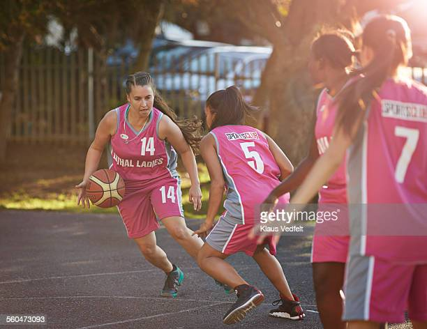 Female basket player dribbles the ball at practice
