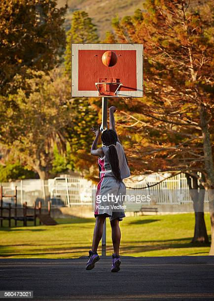 Female basket player practicing at the hoop