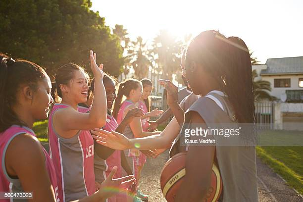 Female basket players doing high five's after game