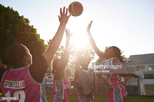 Female basket players jumping to get the ball