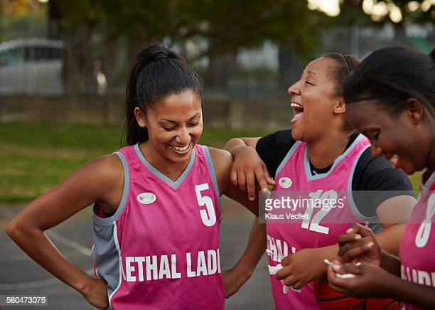 Female basket players laughing after practice