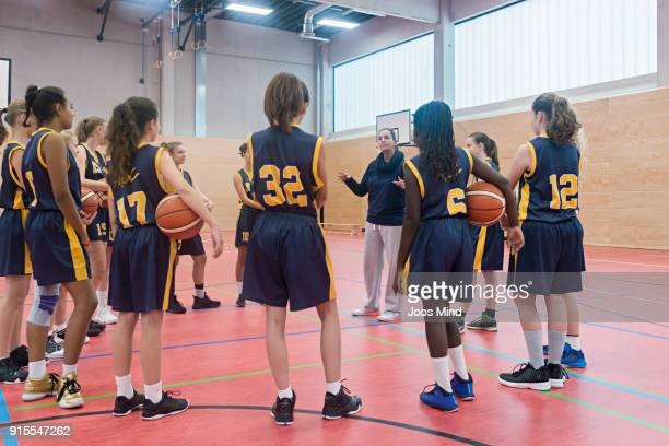 female basketball coach teaching a group of young players - court hearing stockfoto's en -beelden