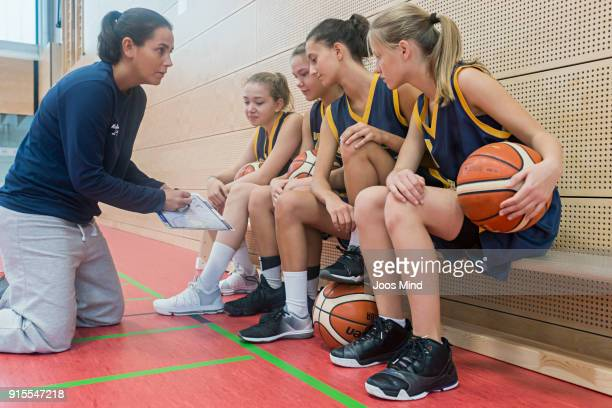 female basketball coach teaching young players, using clipboard - sportkleding stock pictures, royalty-free photos & images