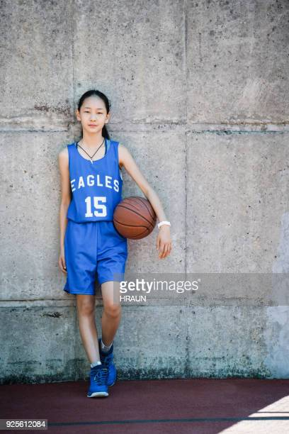 Female basketball player standing with ball