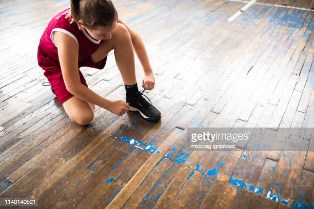 female basketball player tying shoelace - basketball shoe stock photos and pictures