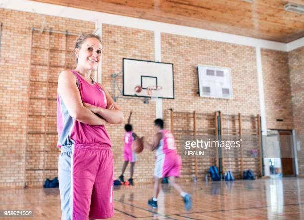 female basketball player with arms crossed in gym - desporto de equipa imagens e fotografias de stock