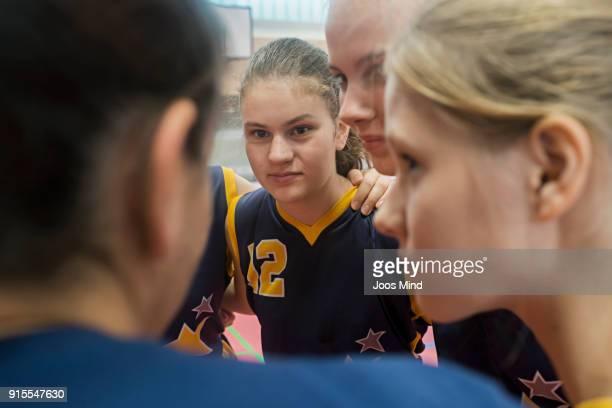 female basketball players and coach huddling together in circle - esporte de equipe - fotografias e filmes do acervo