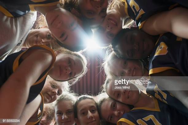 female basketball players and coach huddling together in circle - basketball sport stock pictures, royalty-free photos & images