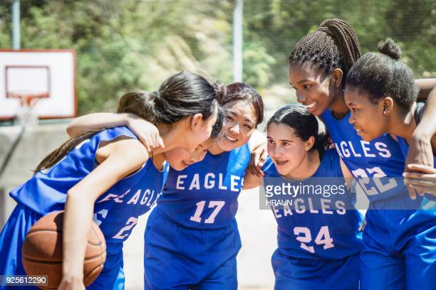 female basketball players huddling on court - basketball team stock pictures, royalty-free photos & images