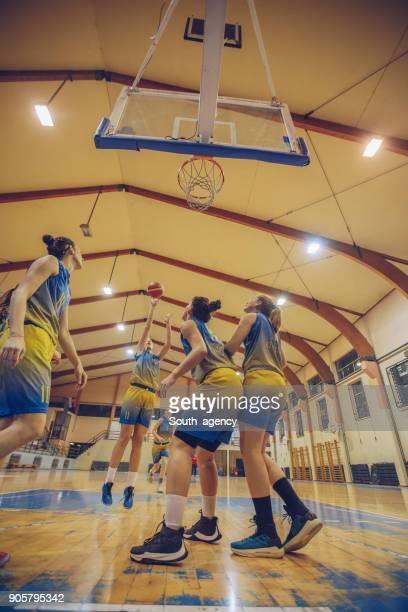 Female basketball players playing basketball