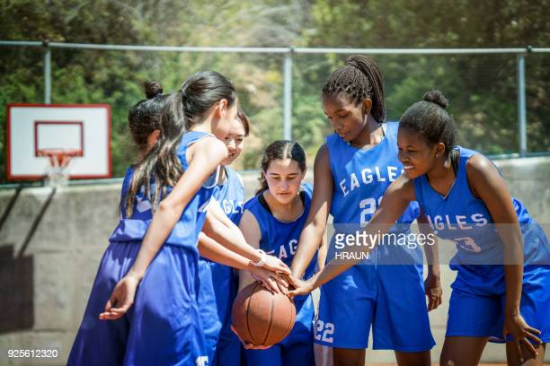 female basketball players stacking hands on ball - basketball team stock pictures, royalty-free photos & images