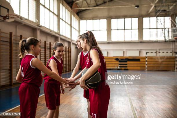 female basketball players stacking hands - basketball team stock pictures, royalty-free photos & images