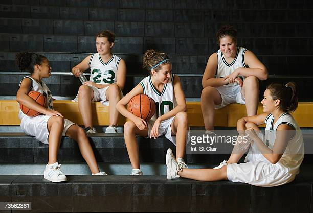 Female basketball team talking on benches