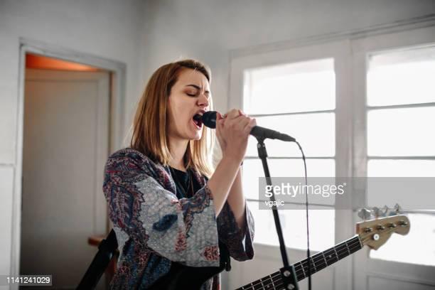 女子バスギタリストのリハーサル - シンガーソングライター ストックフォトと画像